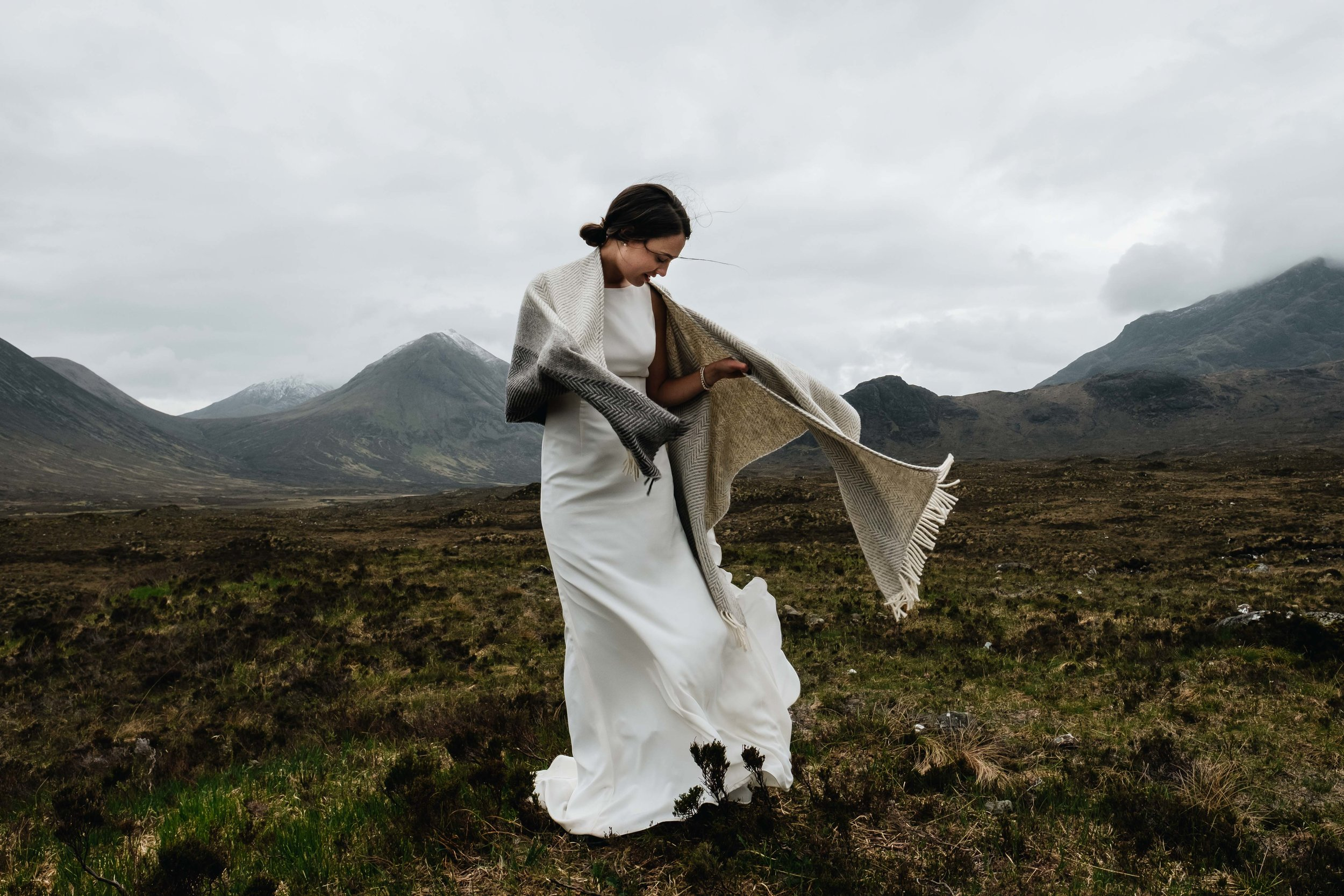 A bride's shawl is being blown in the wind.