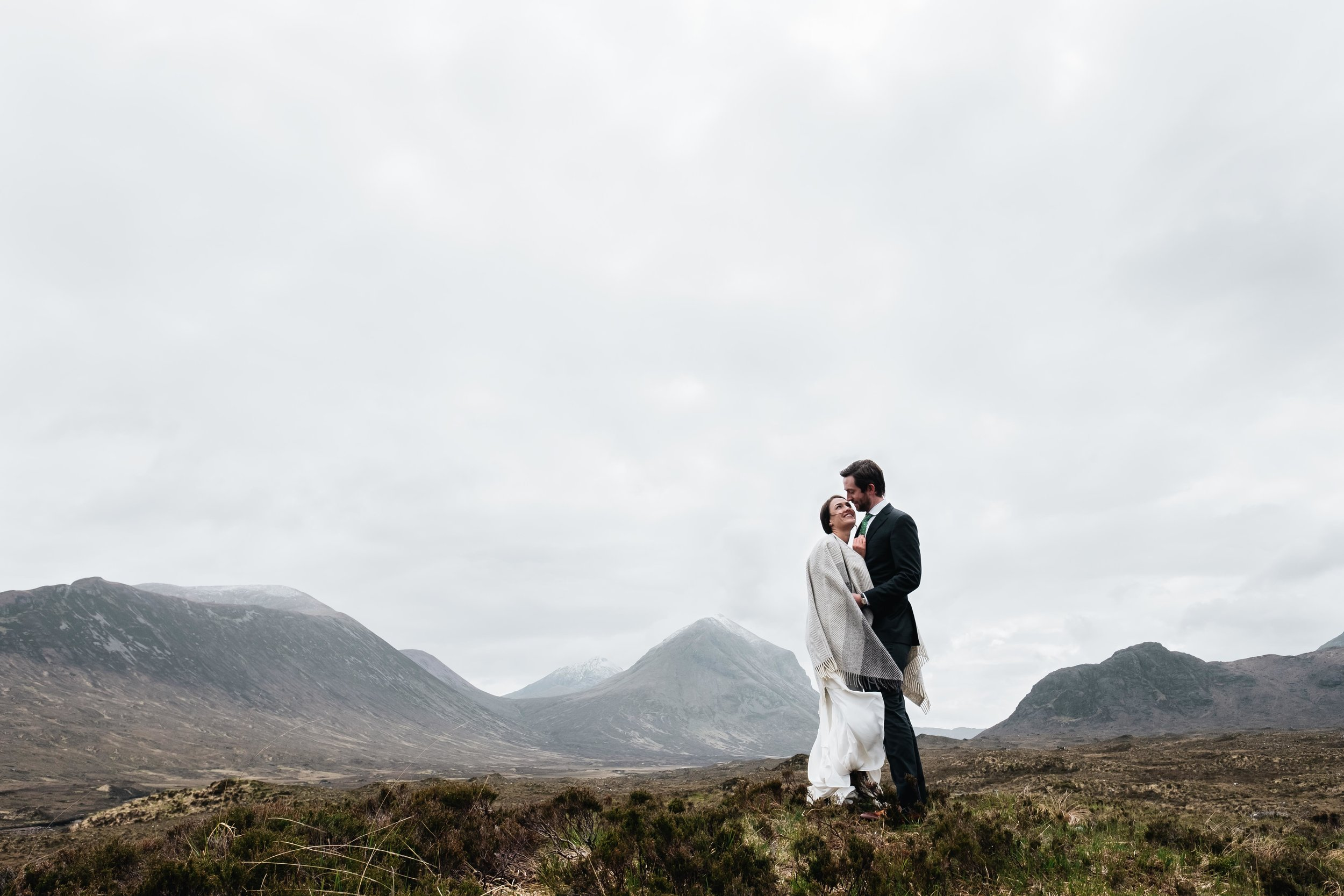 Couple standing  with the Cuillins behind them