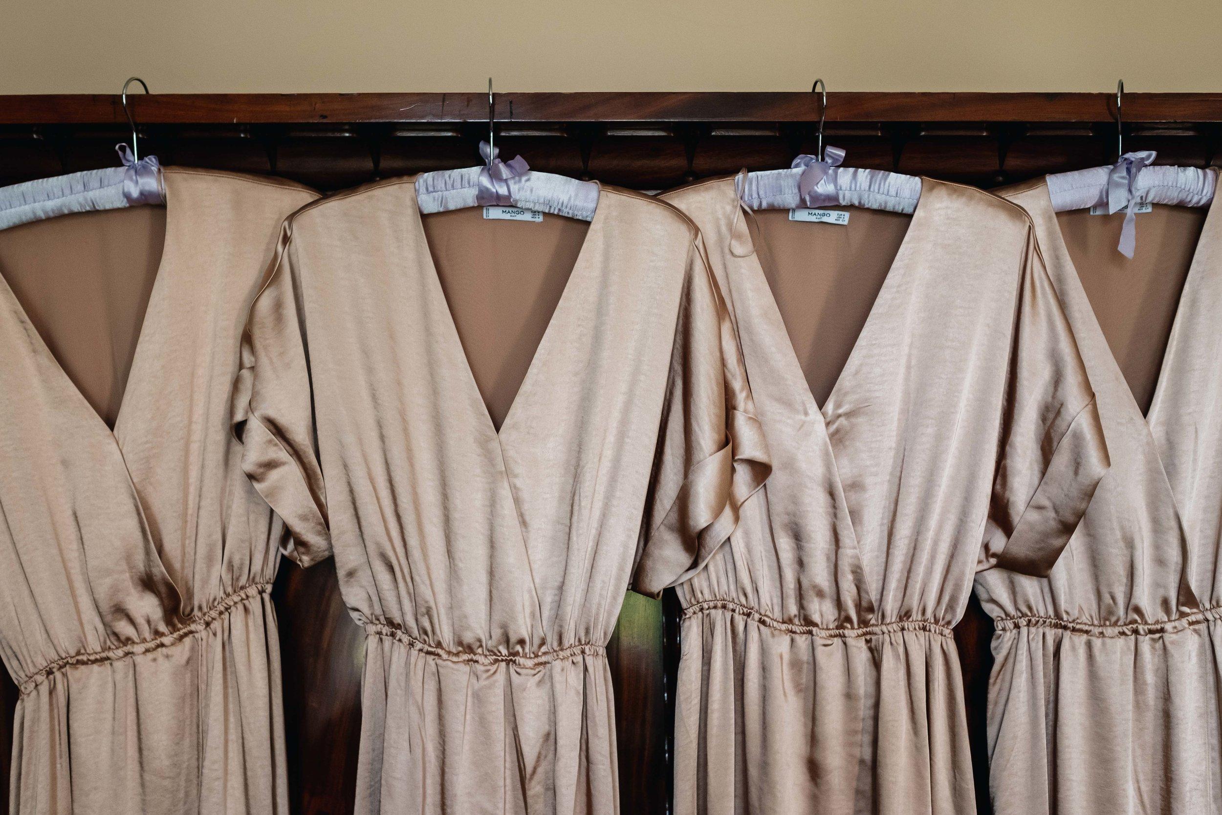 gold bridesmaid dresses hanging on door