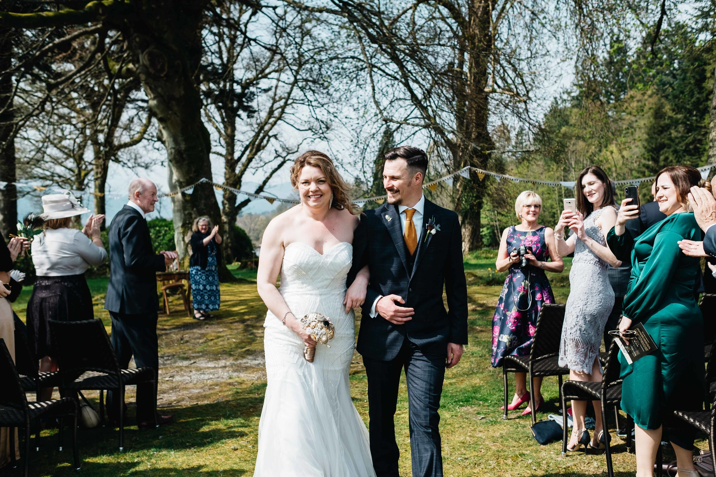 bride and groom smiling as they walk up the aisle of their outdoor wedding ceremony