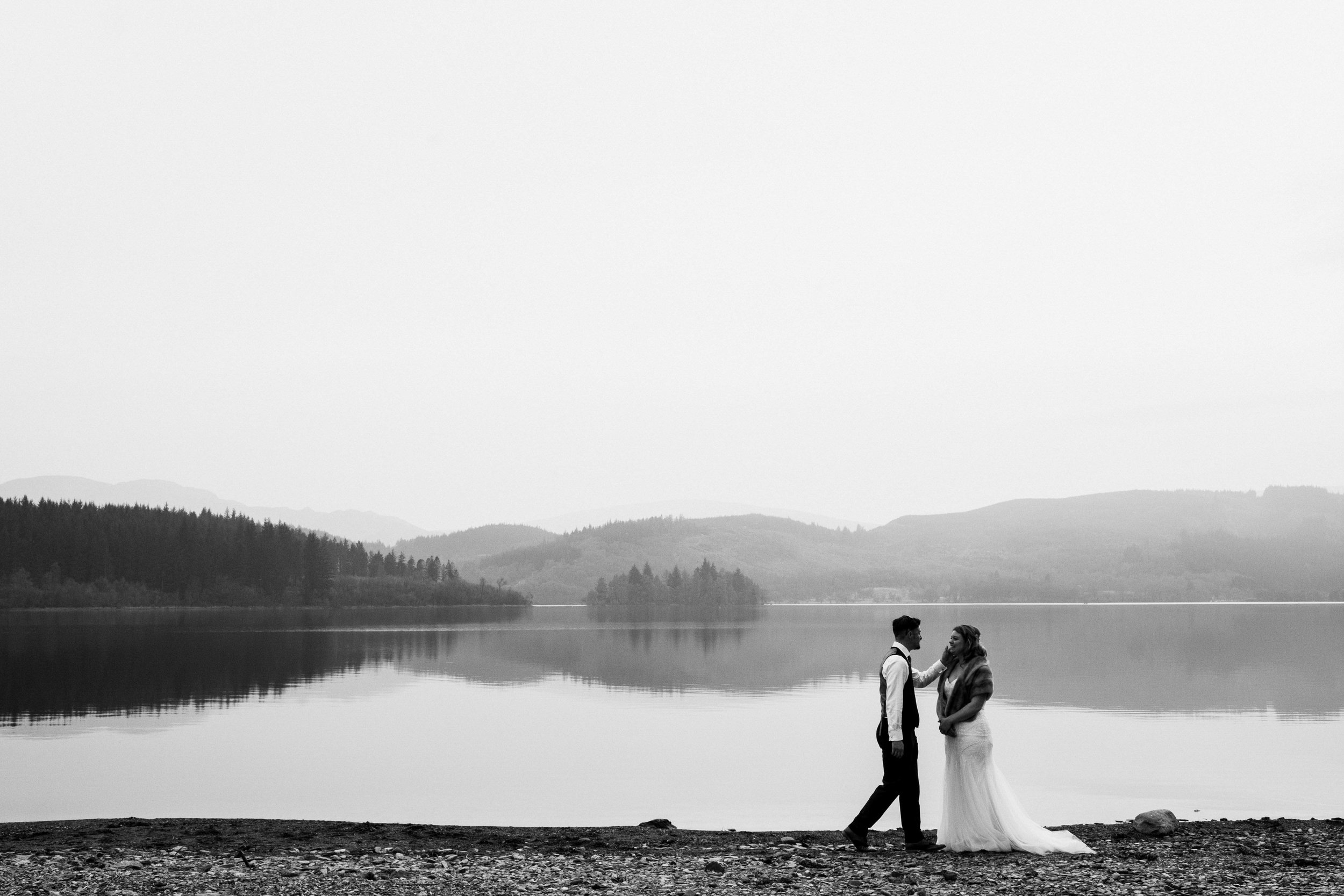 bride and groom walk on the shore of Loch Ard