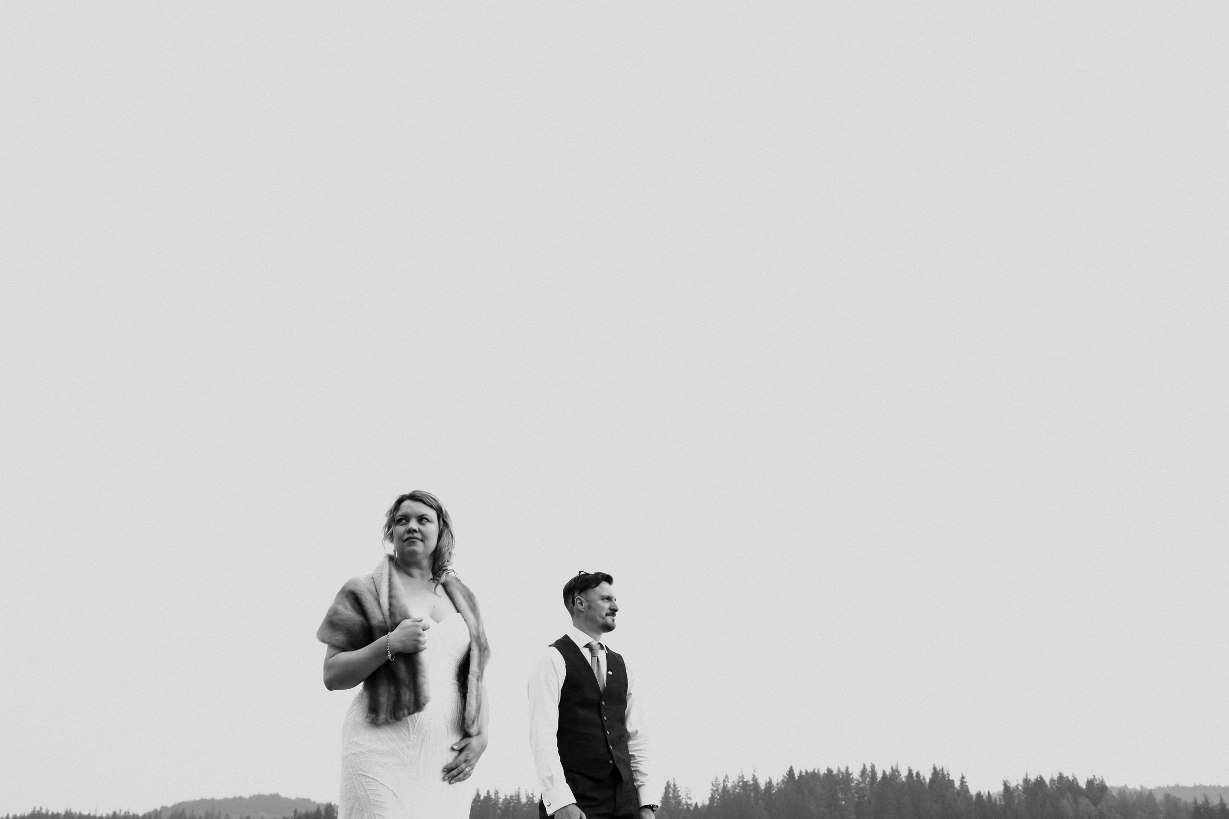 A bride and groom look into the distance and stand apart from each other.