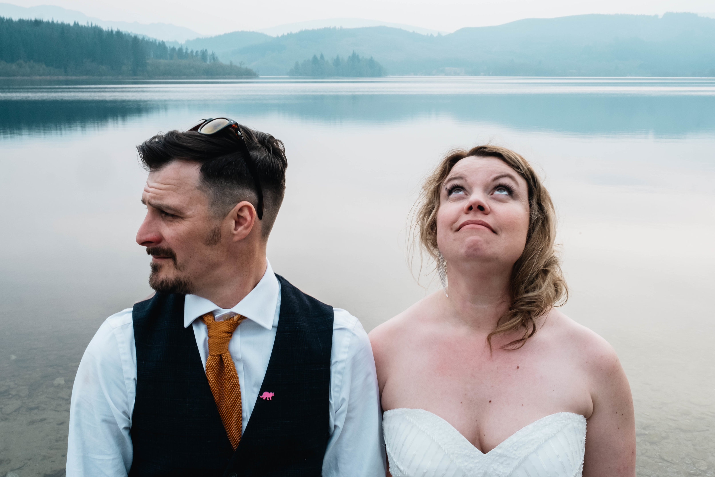 A bride and groom stand next to each other but are lookign in different directions