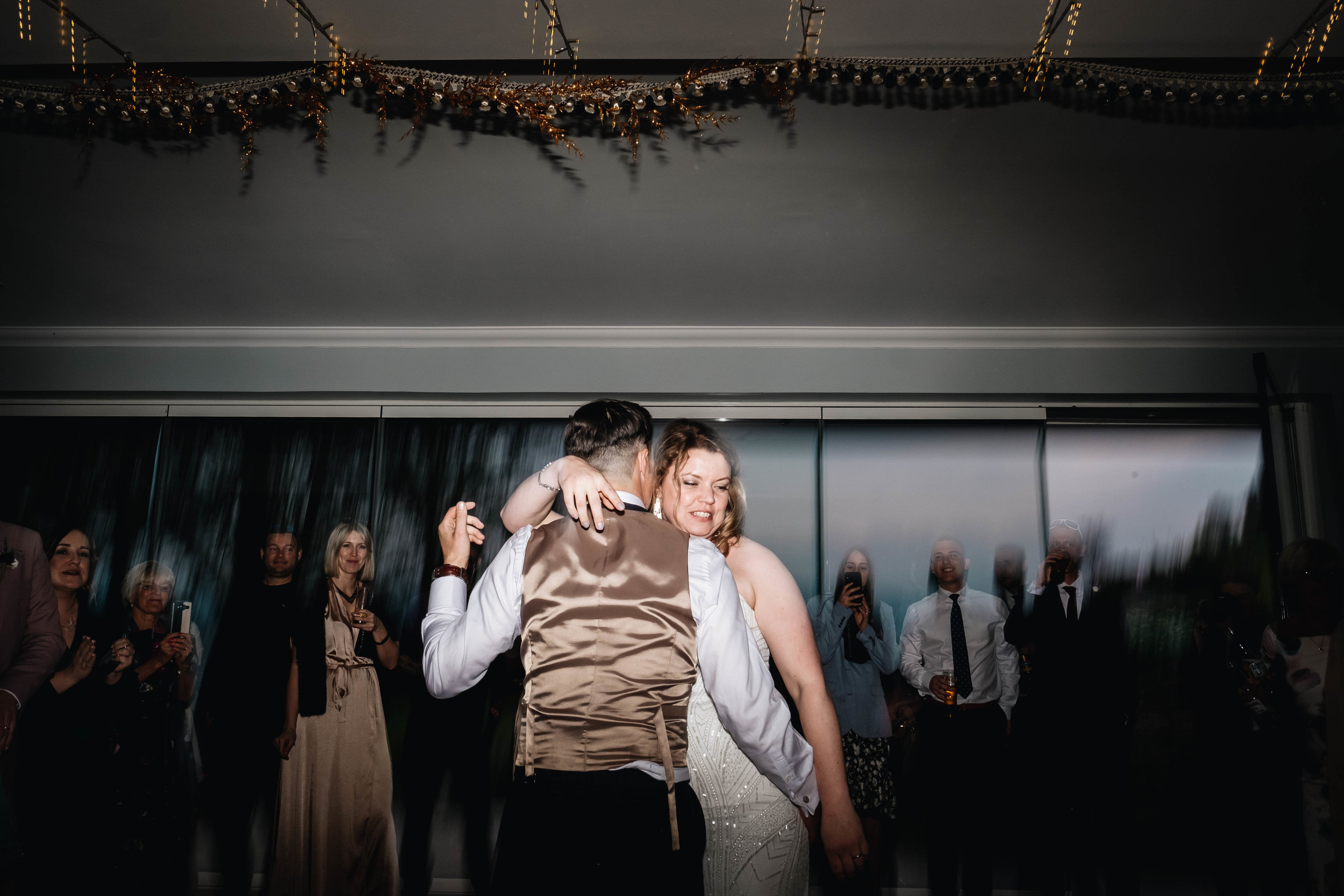First dance and bride is holding onto the neck of her husband.