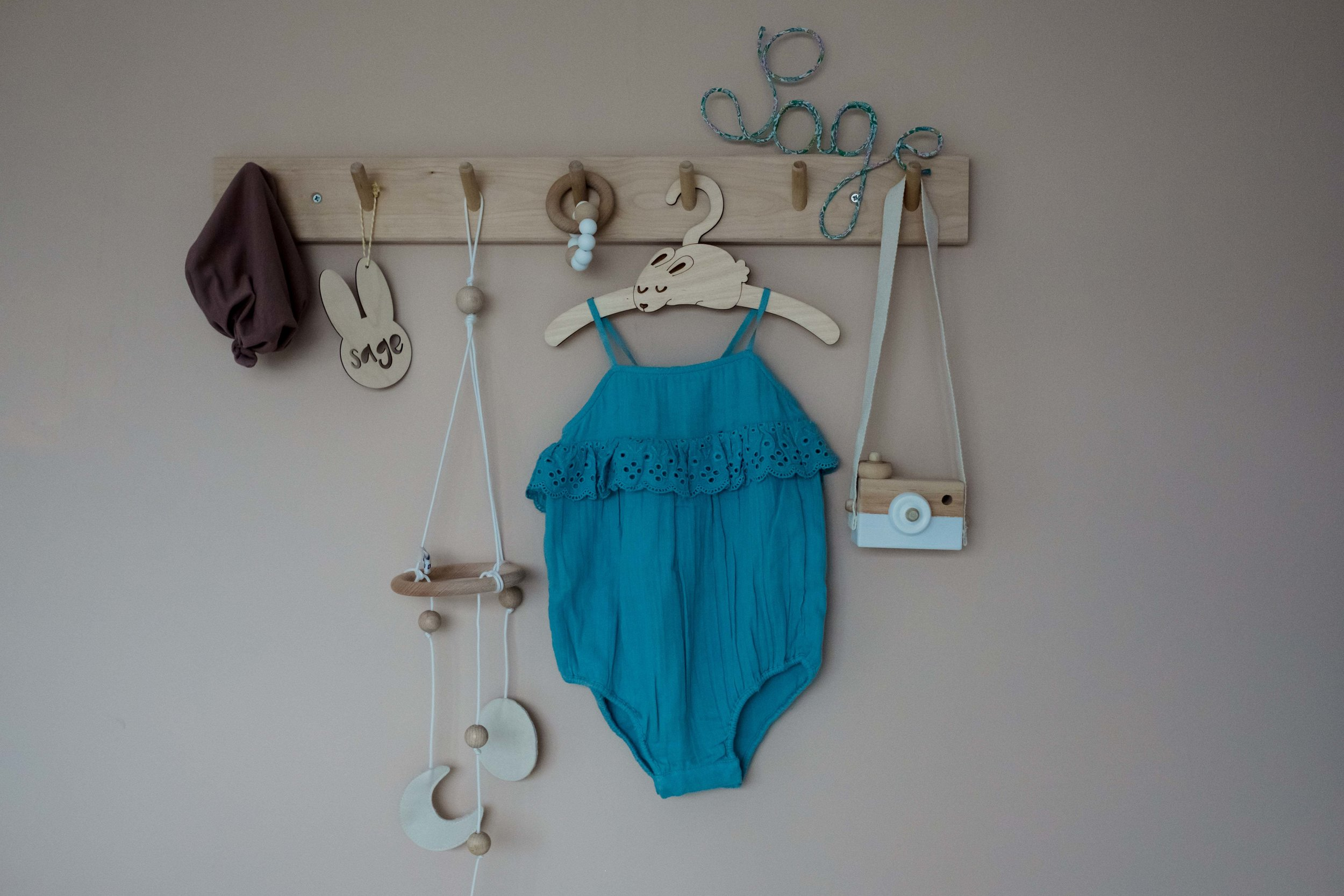 baby girl's clothes are hanging on wall