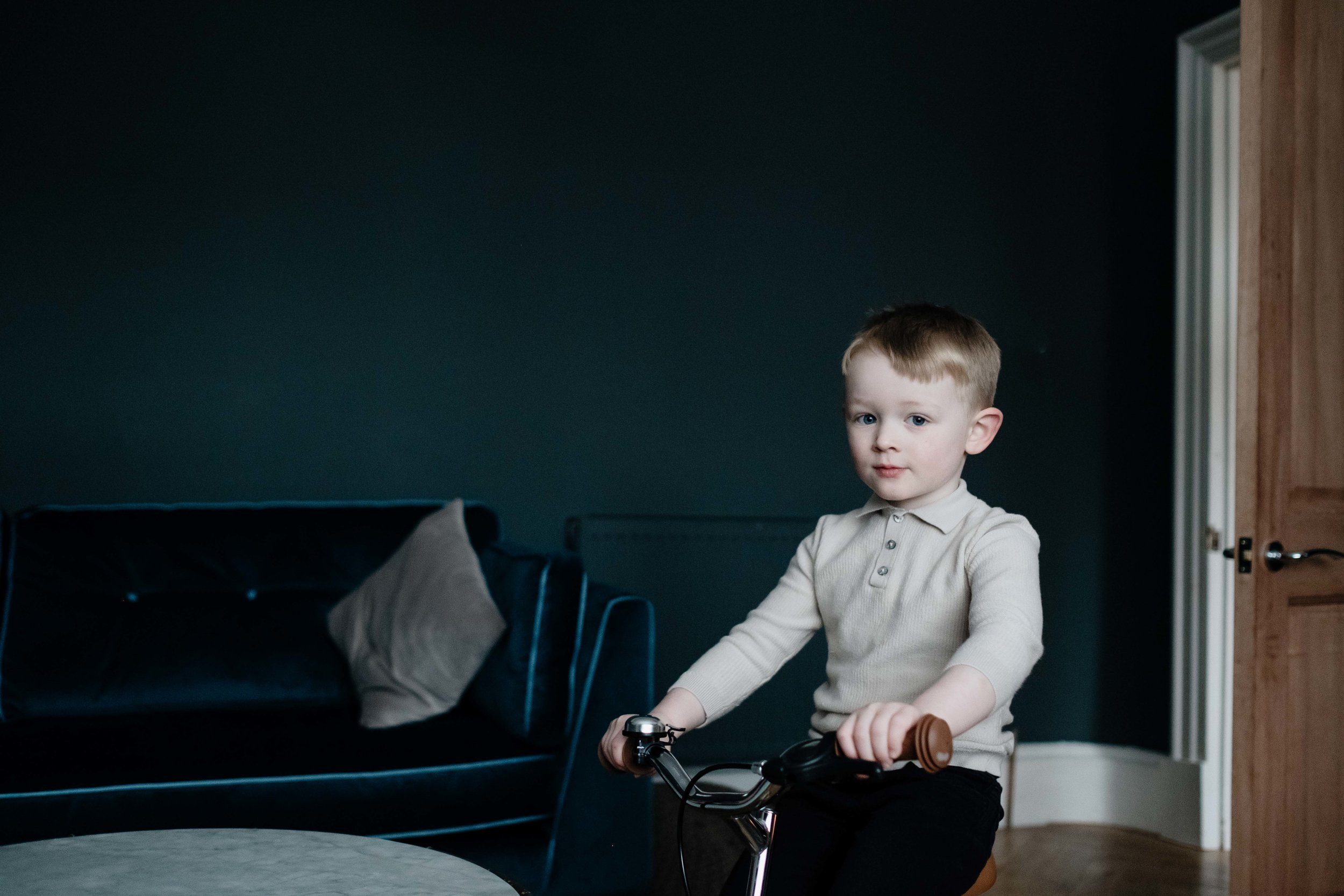 a young boy is sitting on his bike in the living room of his family home