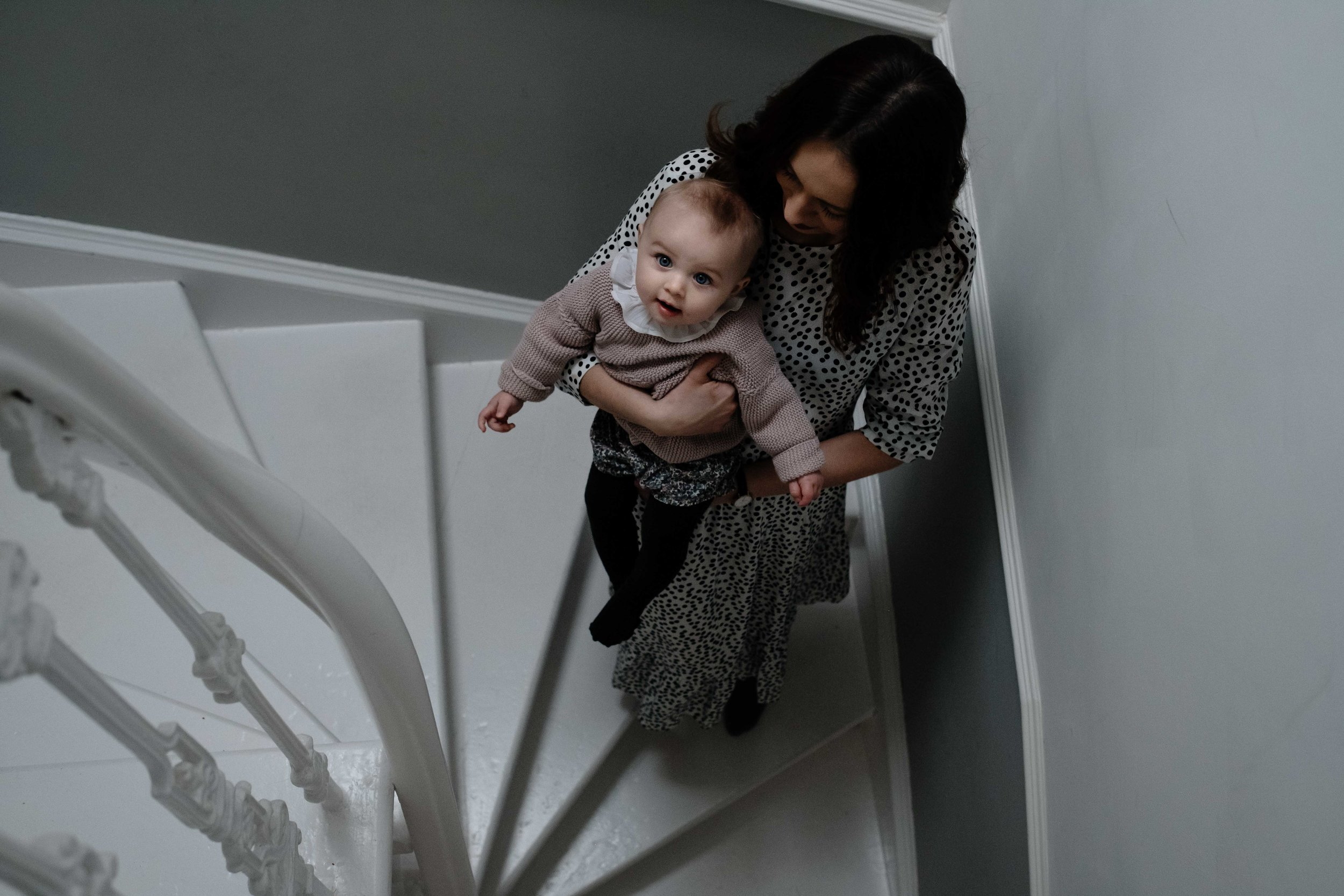 a mother is walking down the stairs of her house carrying her baby daughter