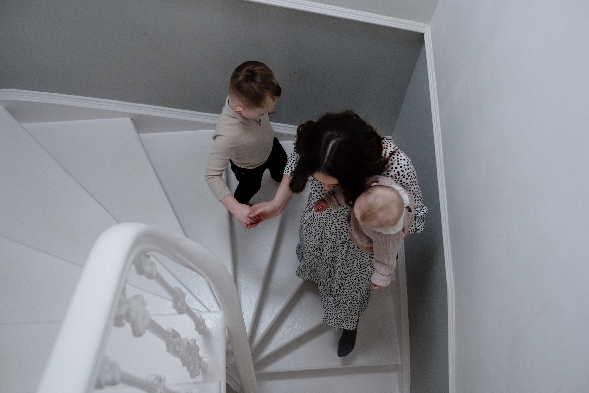 a mother is walking down the stairs of her house carrying her baby daughter and holding her son's hand.