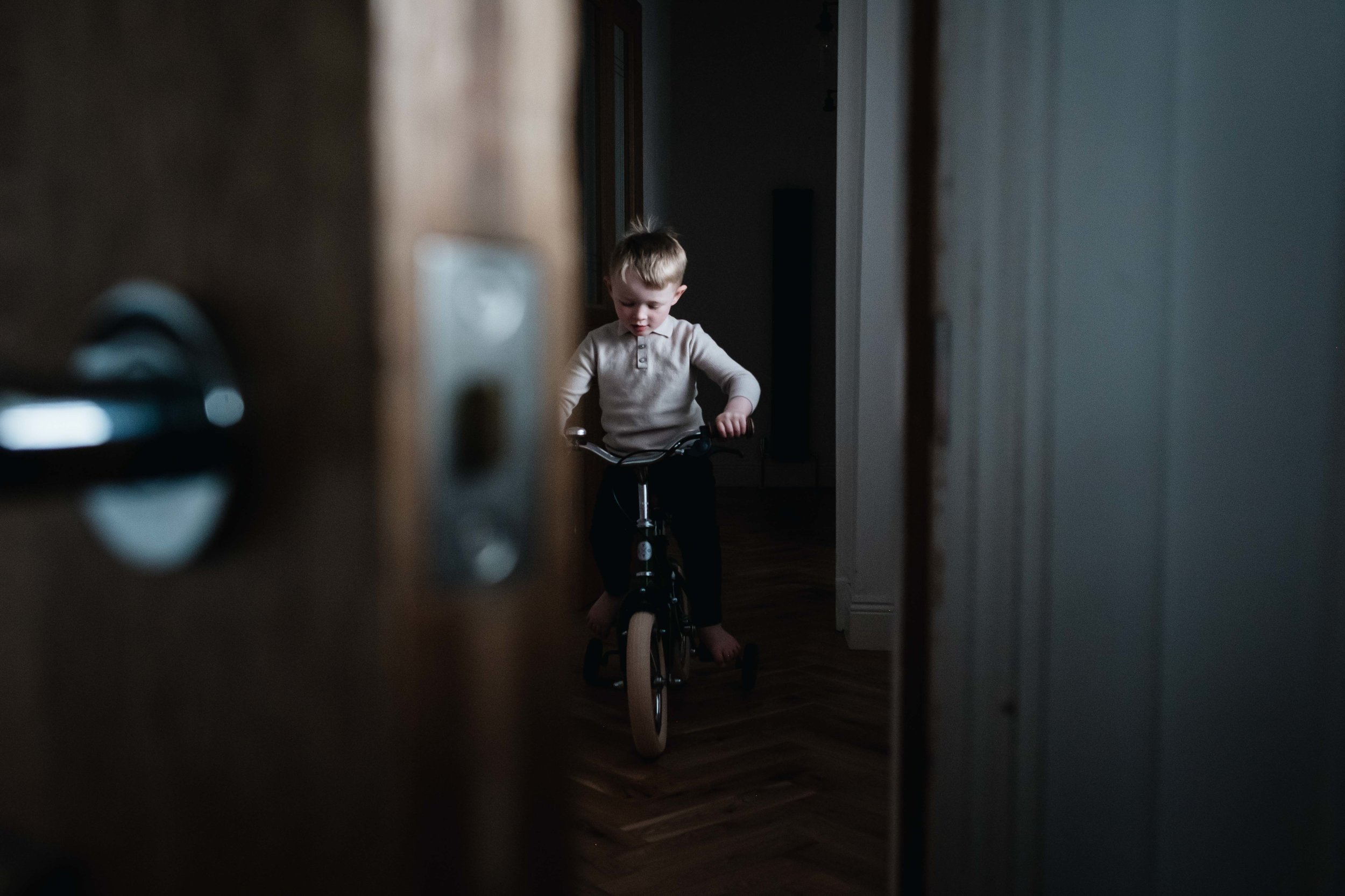 a young boy is riding his vintage bike in his family home