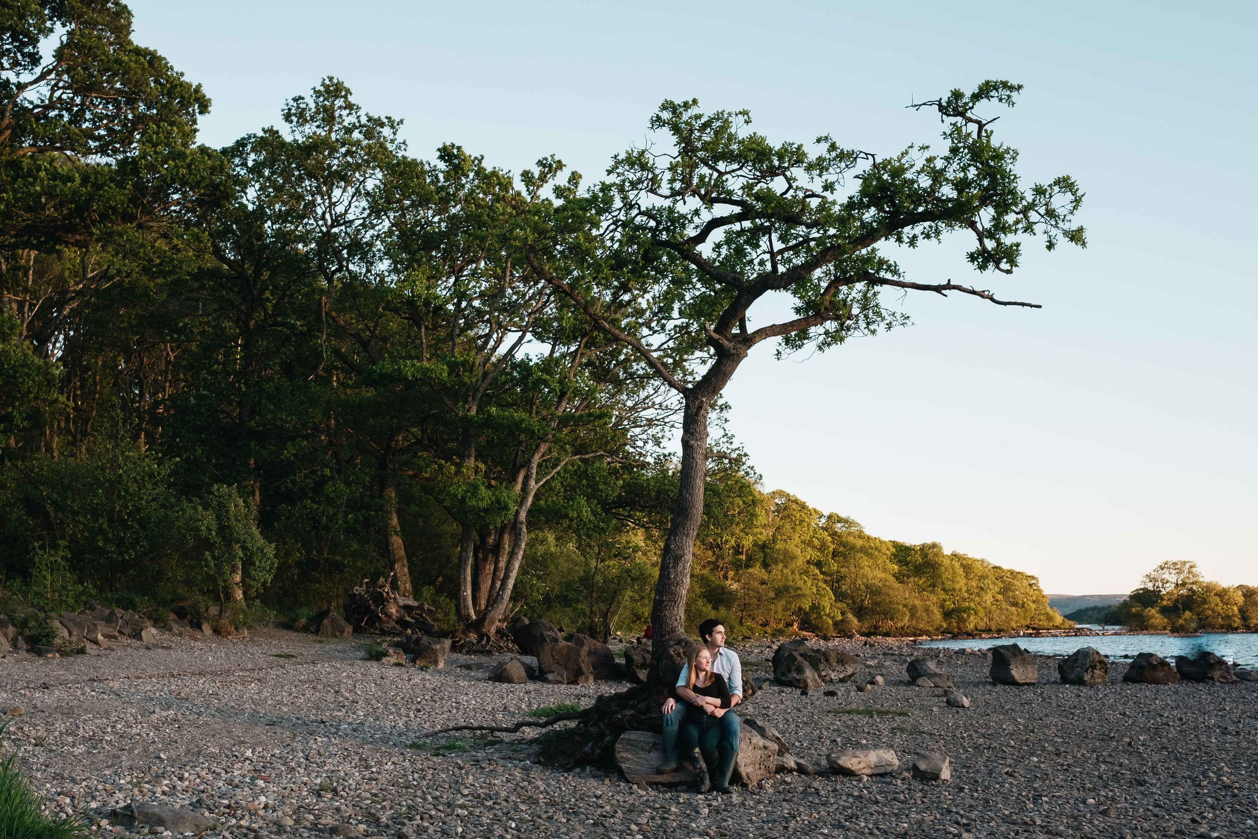 Couple sitting under a tree at Milarrochy Bay.