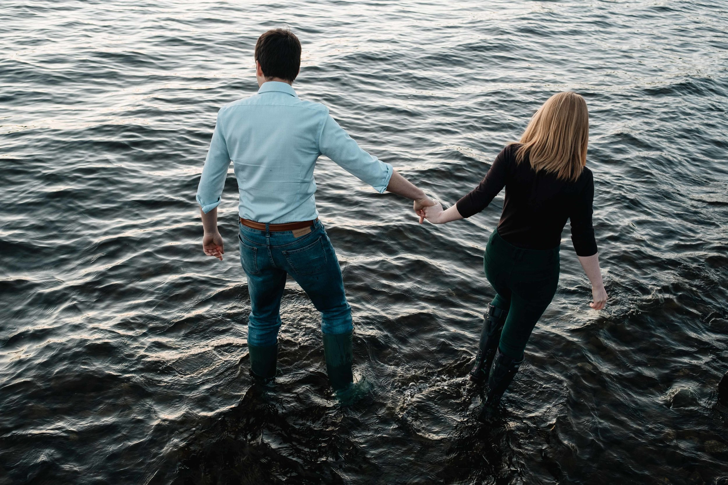Couple are walking in water.