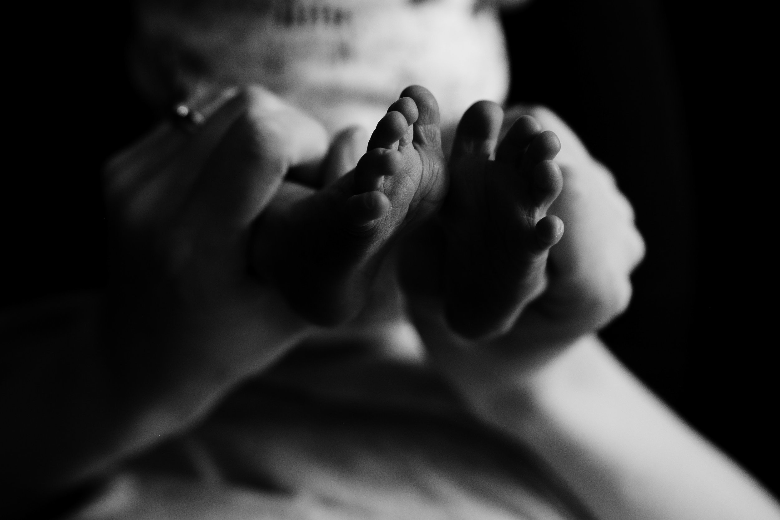 mother holding the feet of her newborn in her hands
