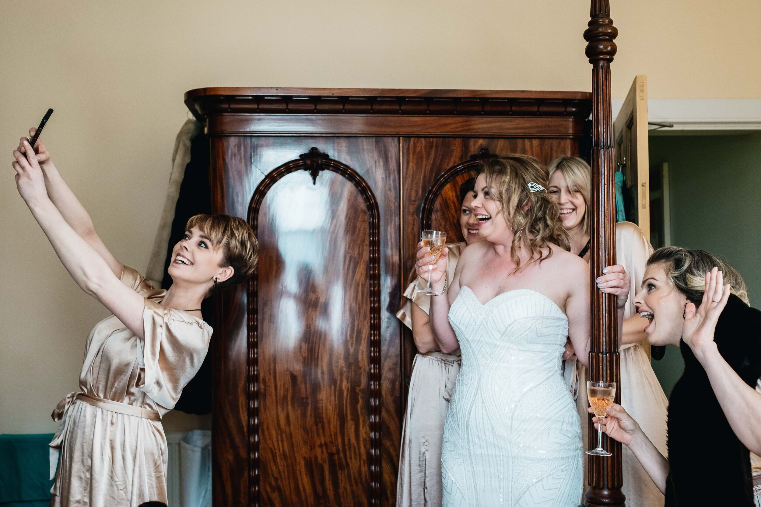 Bridesmaids take a selfie of the other bridesmaids and bride