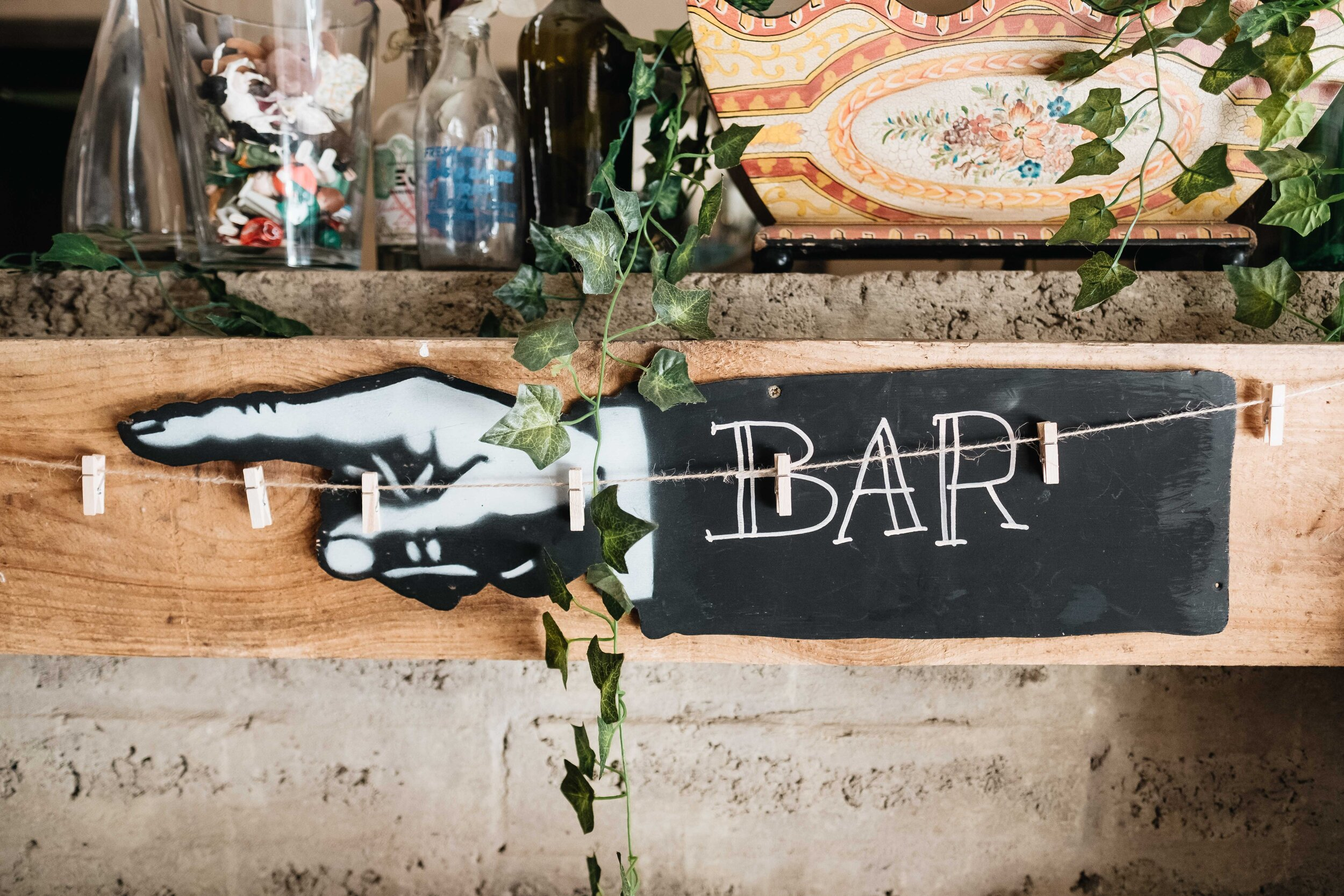 Sign pointing in the direction of the bar and in the shape of a pointing hand.