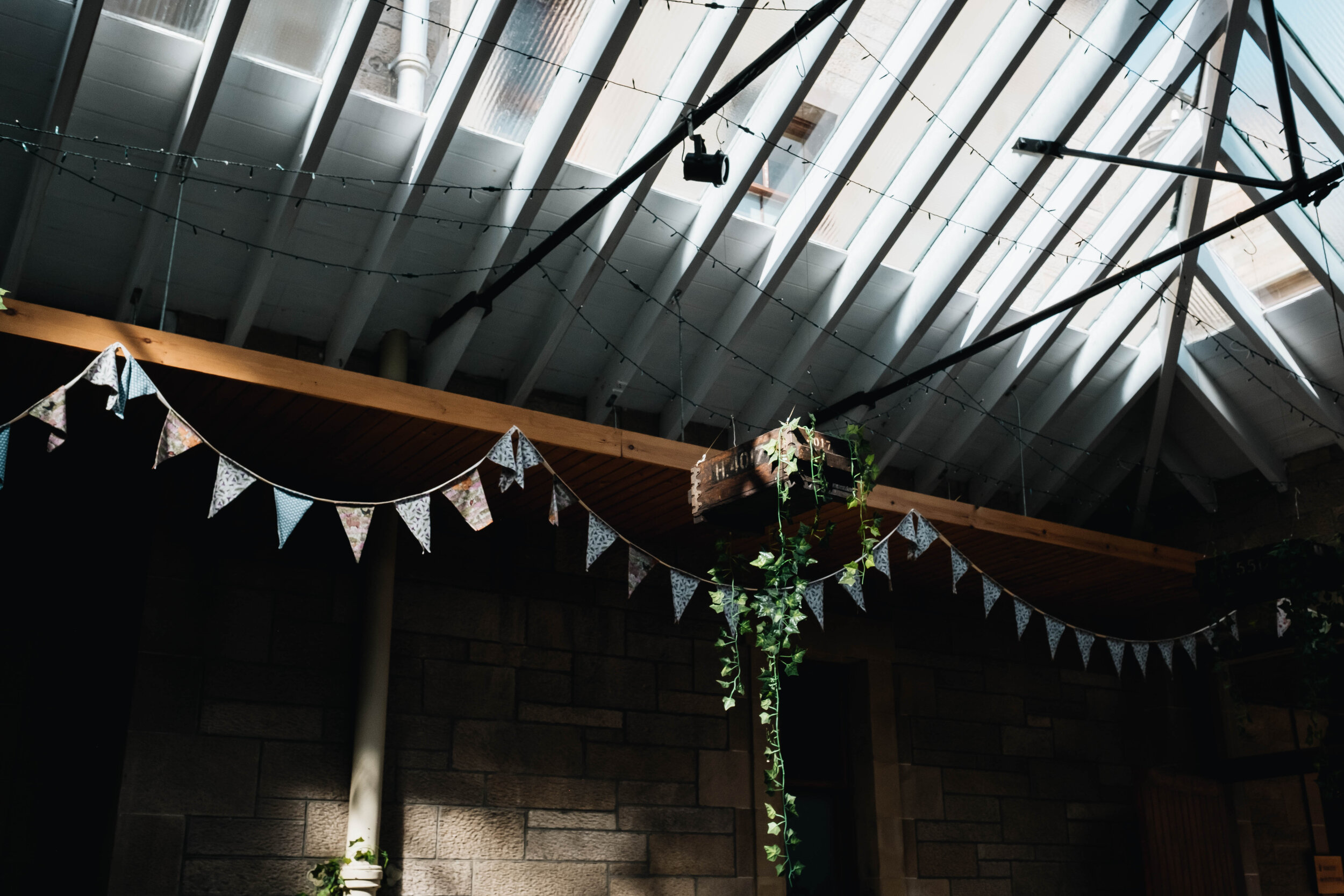 Pastel coloured bunting hangs in the stable area of Cambo House