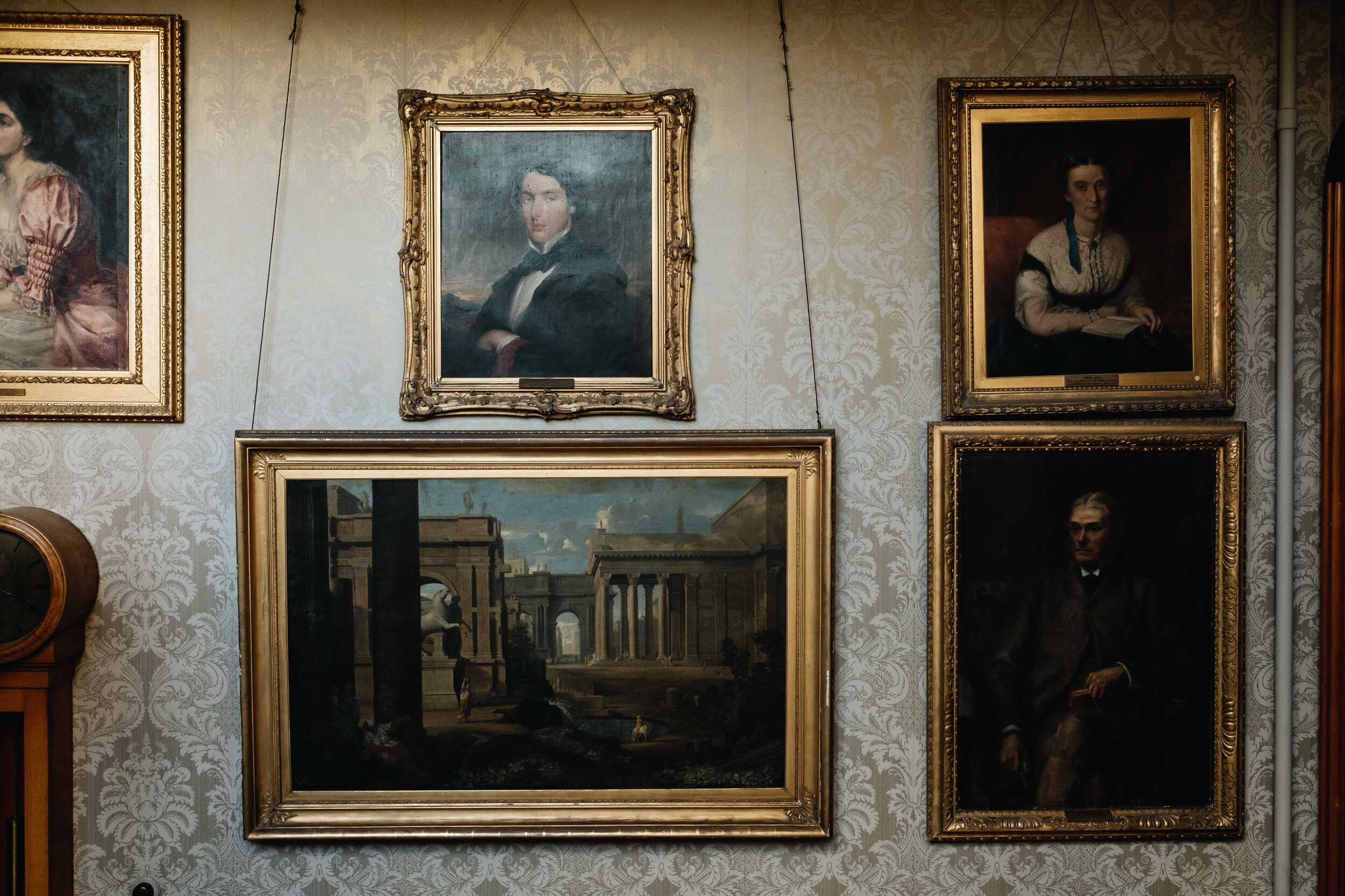 One of the hallway walls of Cambo House which has many paintings with heavy gold frames
