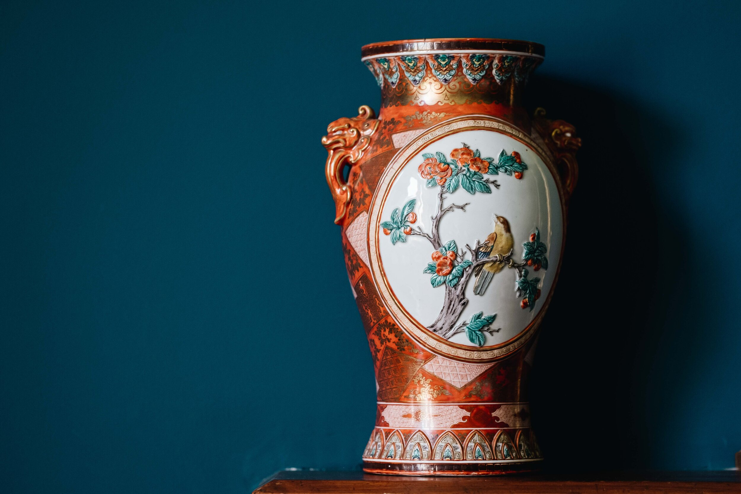 An ornate vase with bird sits on the mantle piece of the blue room in Cambo House.