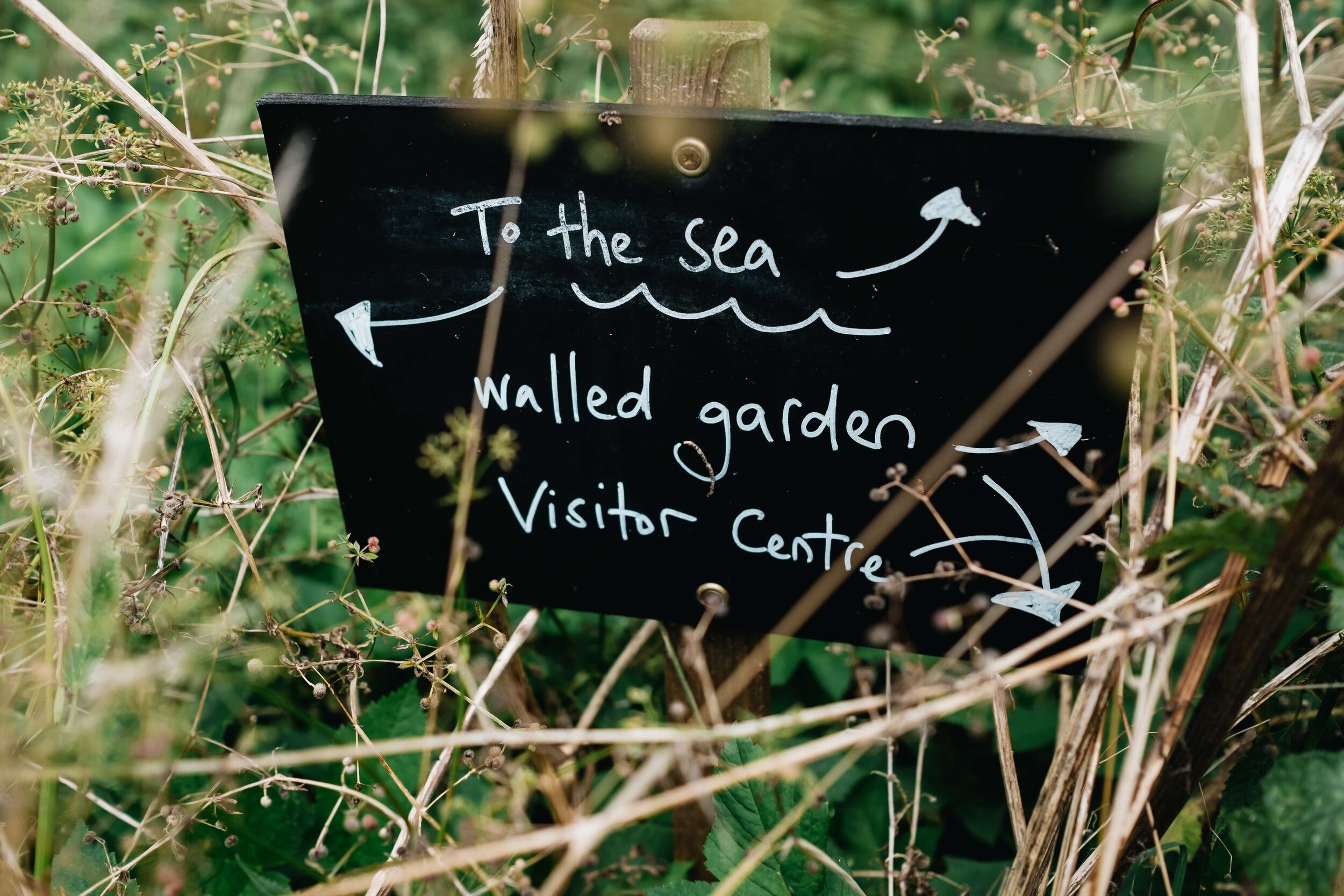 A black sign with white handwriting showing the direction of the sea and walled garden.