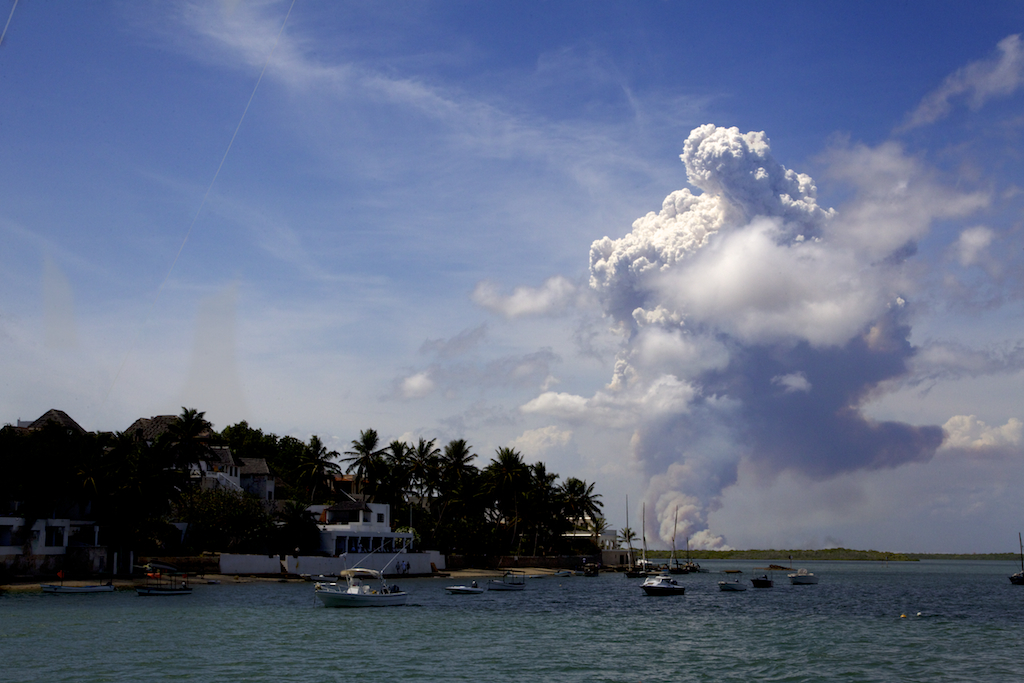 Plumes of smoke rise from the building site for Lamu Port. To the left is the idyllic fishing village of Shela, Lamu island.