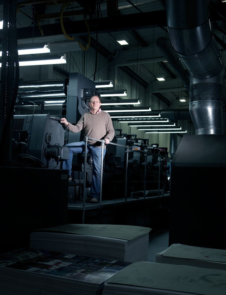 Bruce next to the cold foil machine and below his original concept drawings