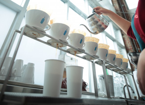 "Blue Bottle Coffee raises the coffee bar. A barista using  the ""pour over"" method on a drip bar. (Picture: Epoch Times)"