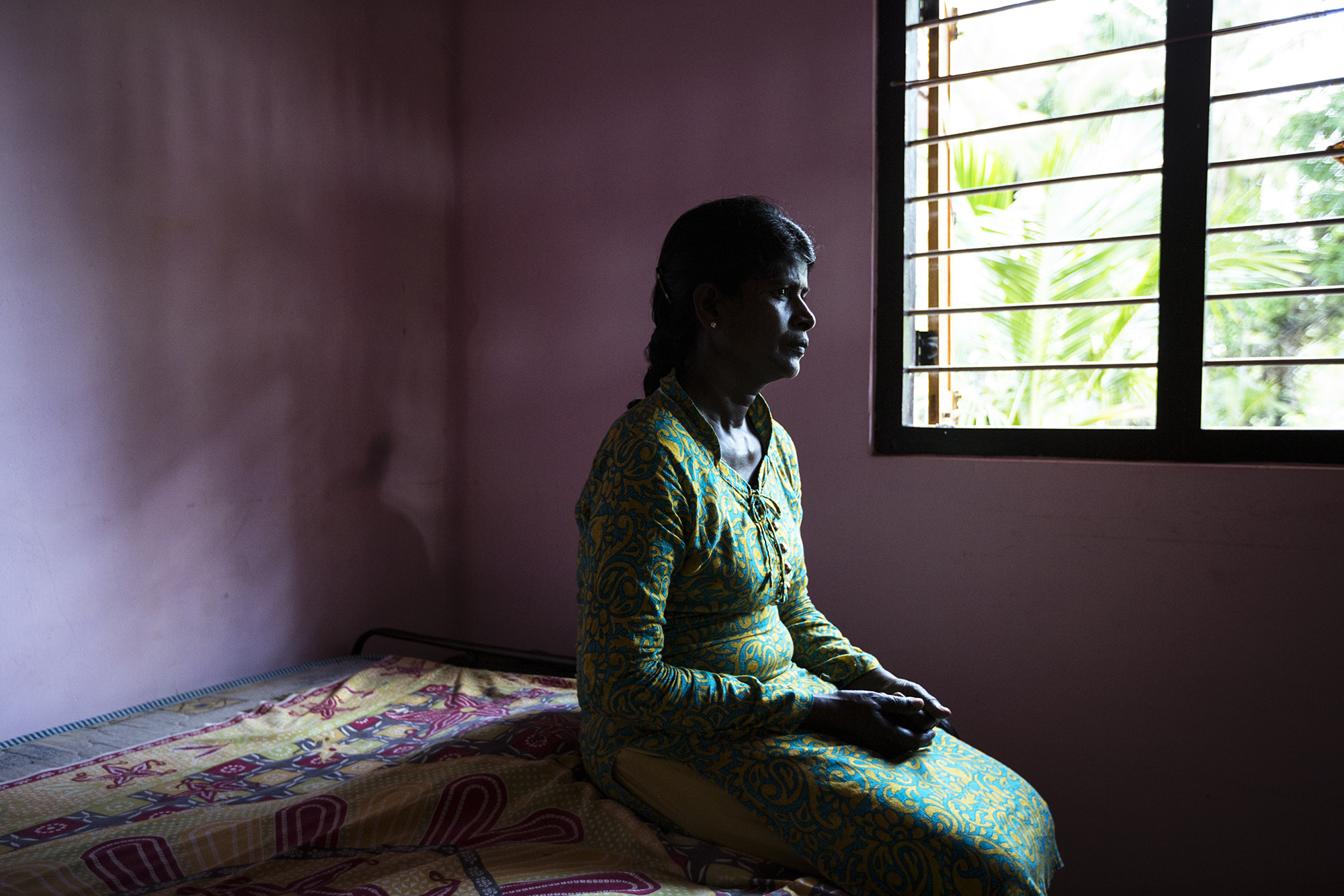 Iruthayarani, 36. Iruthayarani's husband was shot and killed in an open field while she was pregnant with their first child. She and her infant son lived in Cheddikulam displacement camp until they left the camp in 2012 to live on a small plot of jungle land allocated by the government.