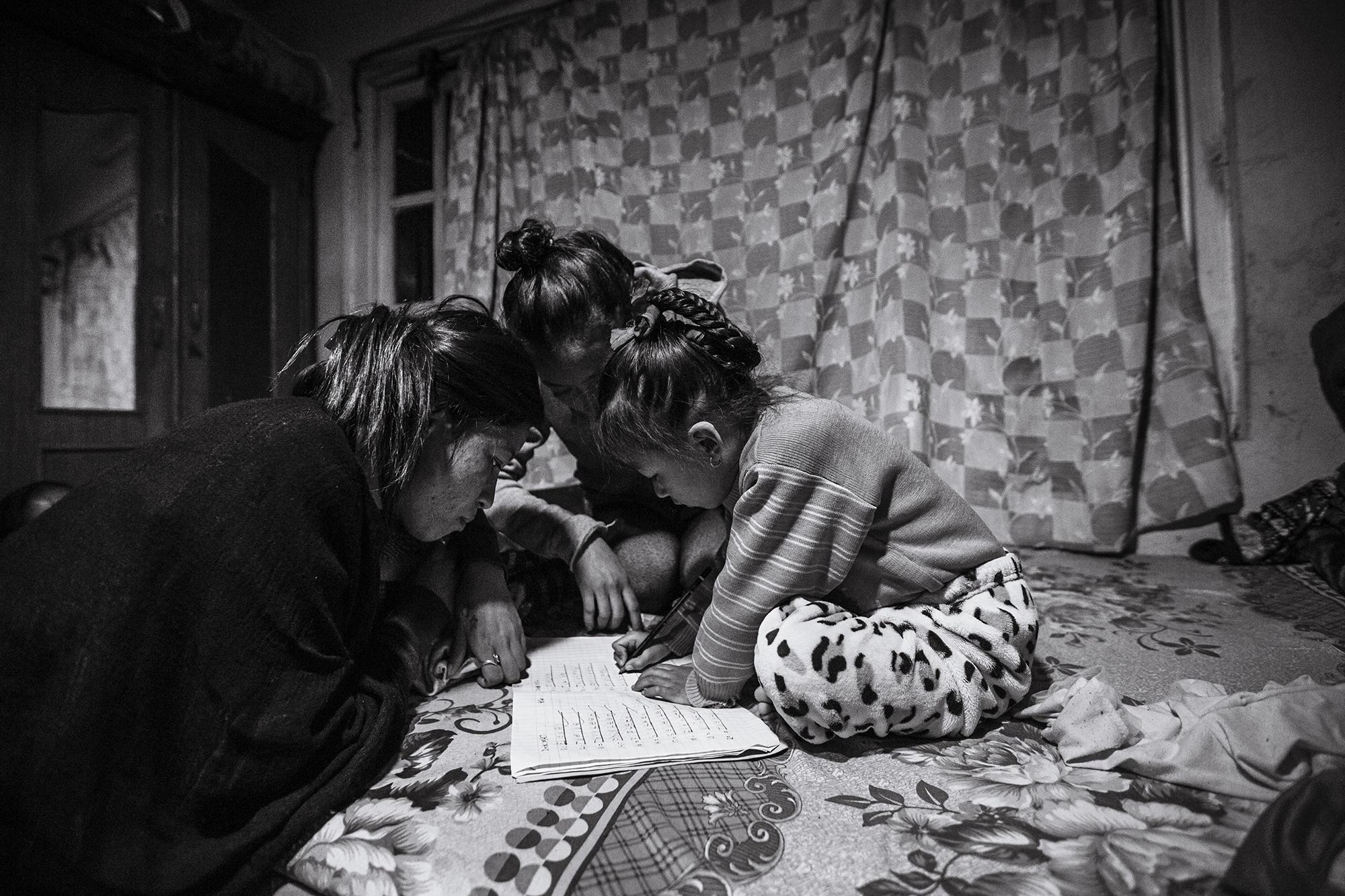 Anu & Anita help Anjika with her schoolwork.