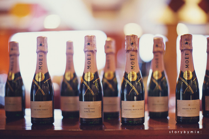 Mini Moet bottles with custom labels as escort cards.