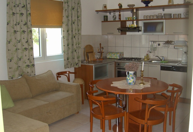 Kjøkken med oppvaskmaskin, kaffetrakter og utstyre til matlaging. Kjøleskap med liten fryser.