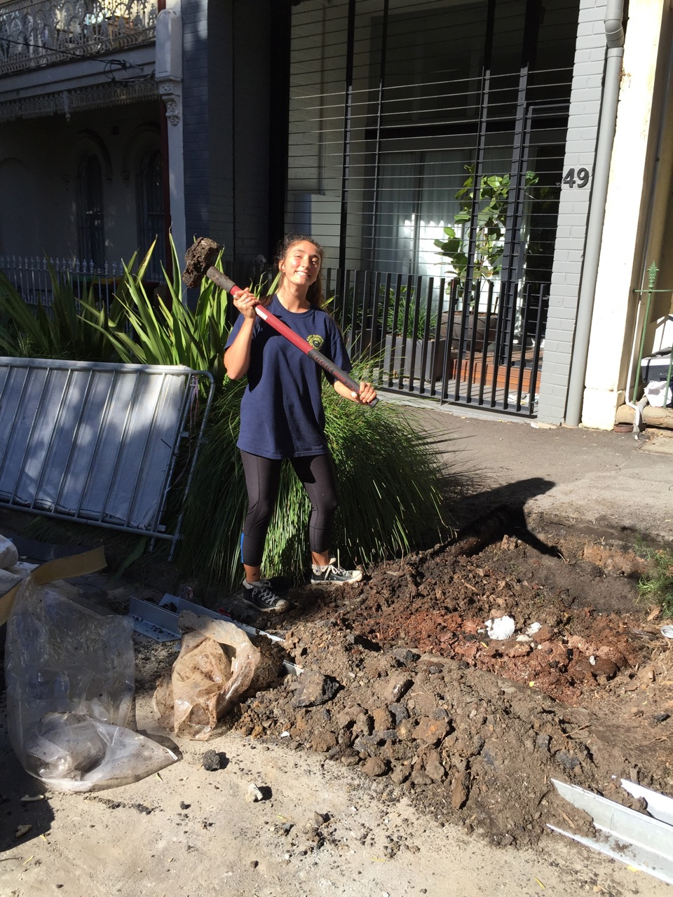 Serena with sledge hammer breaking up rocks to get a good rocky base for the lime and prevent it drowning in water.