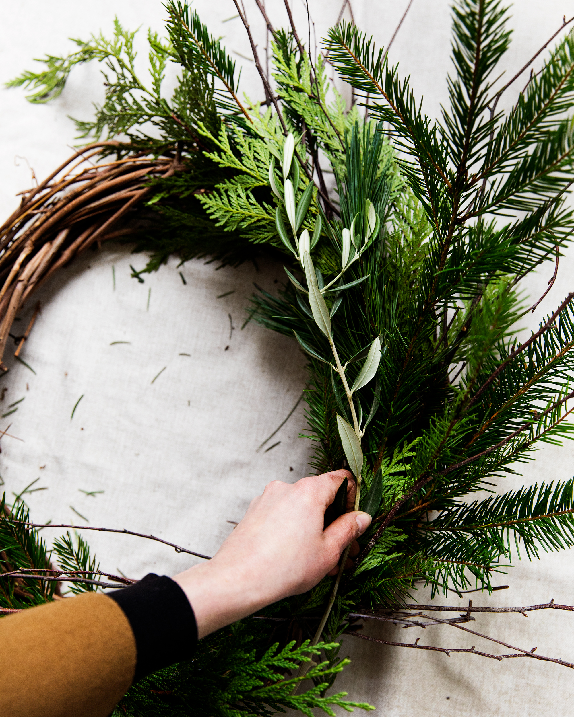 Step Four - Begin layering in the rosemary, and olive branch pieces, tucking them securely into place within the wreath as you go. To create a varied look within the shades of green, flip certain pieces of evergreen over to reveal a lighter or darker color.