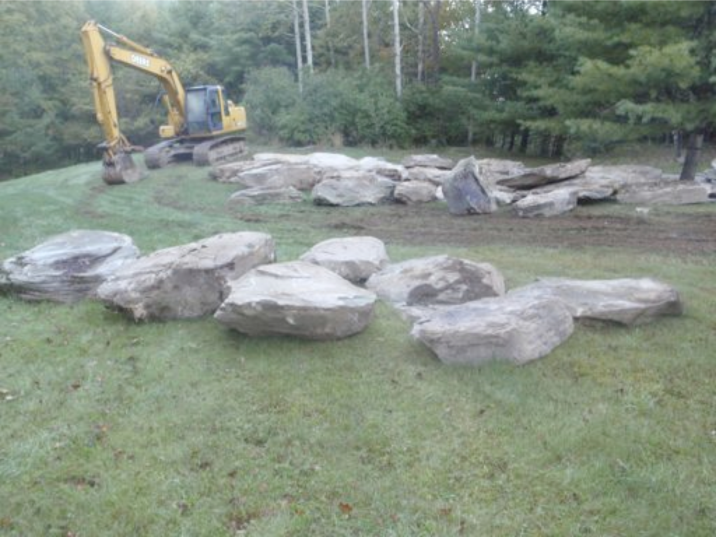 Escavator and Boulders prior to placement.