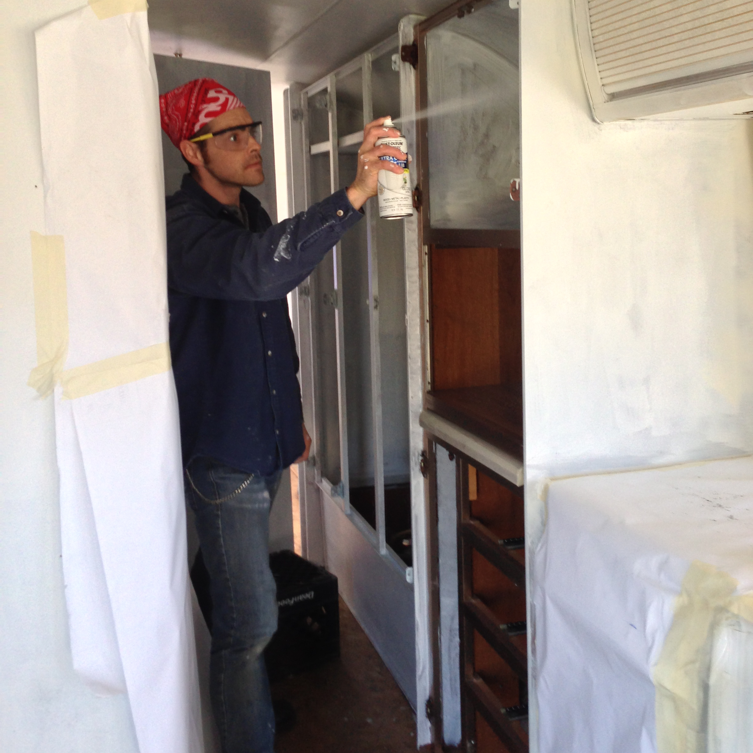 Michael trimming the interior of cabinets with spray paint.