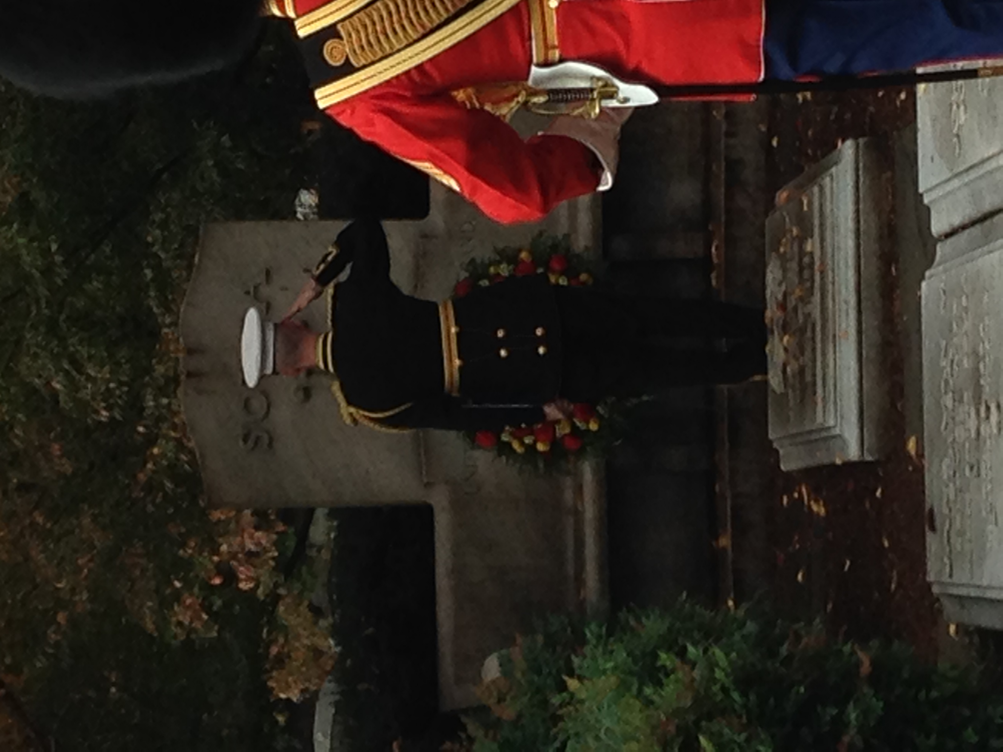 The leader of the band lays a wreath at Sousa's grave and offers a salute.