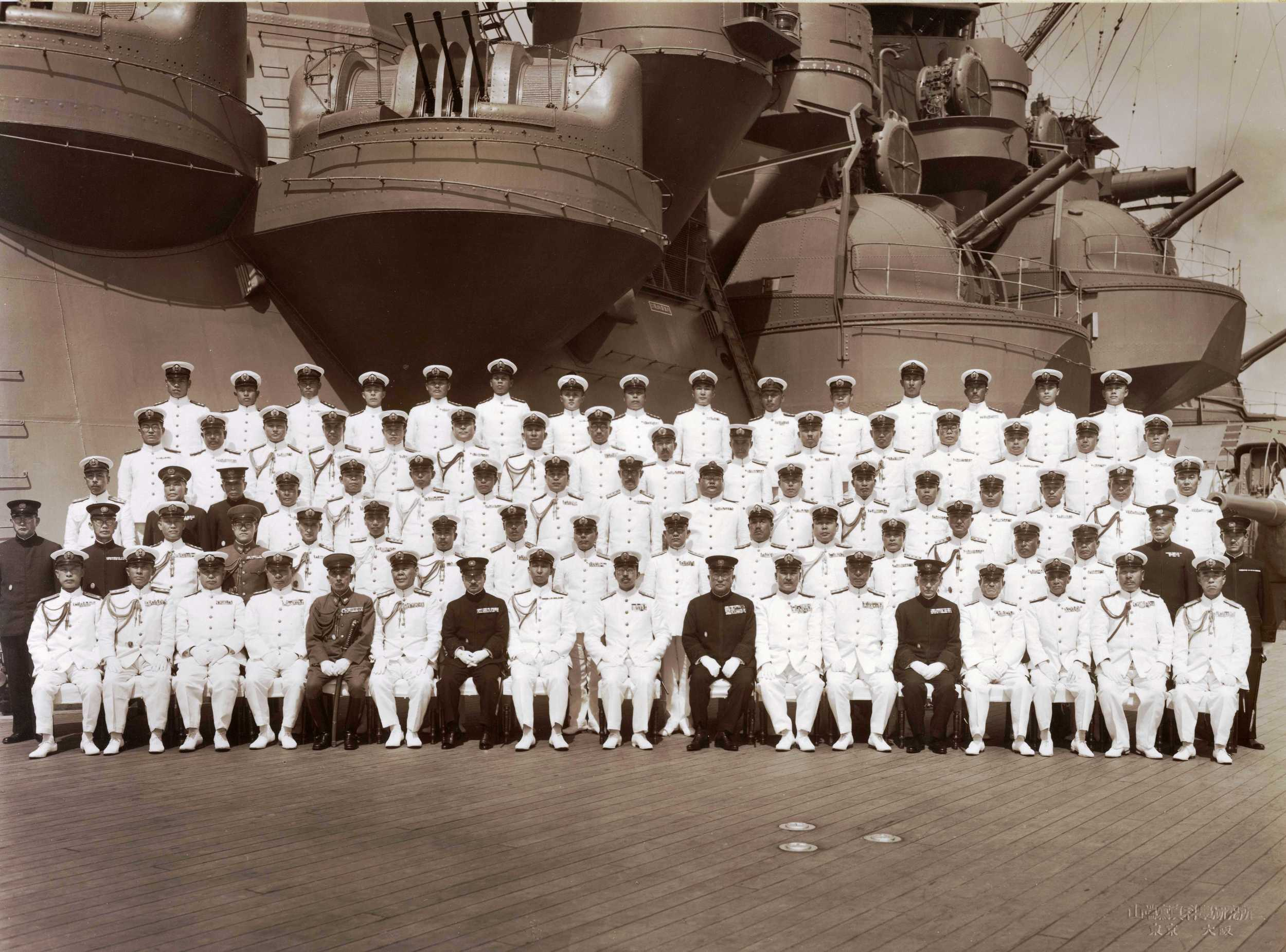Japanese Emperor Hirohito and his staff pictured alongside the ship's crew aboard the Musashi in 1943.