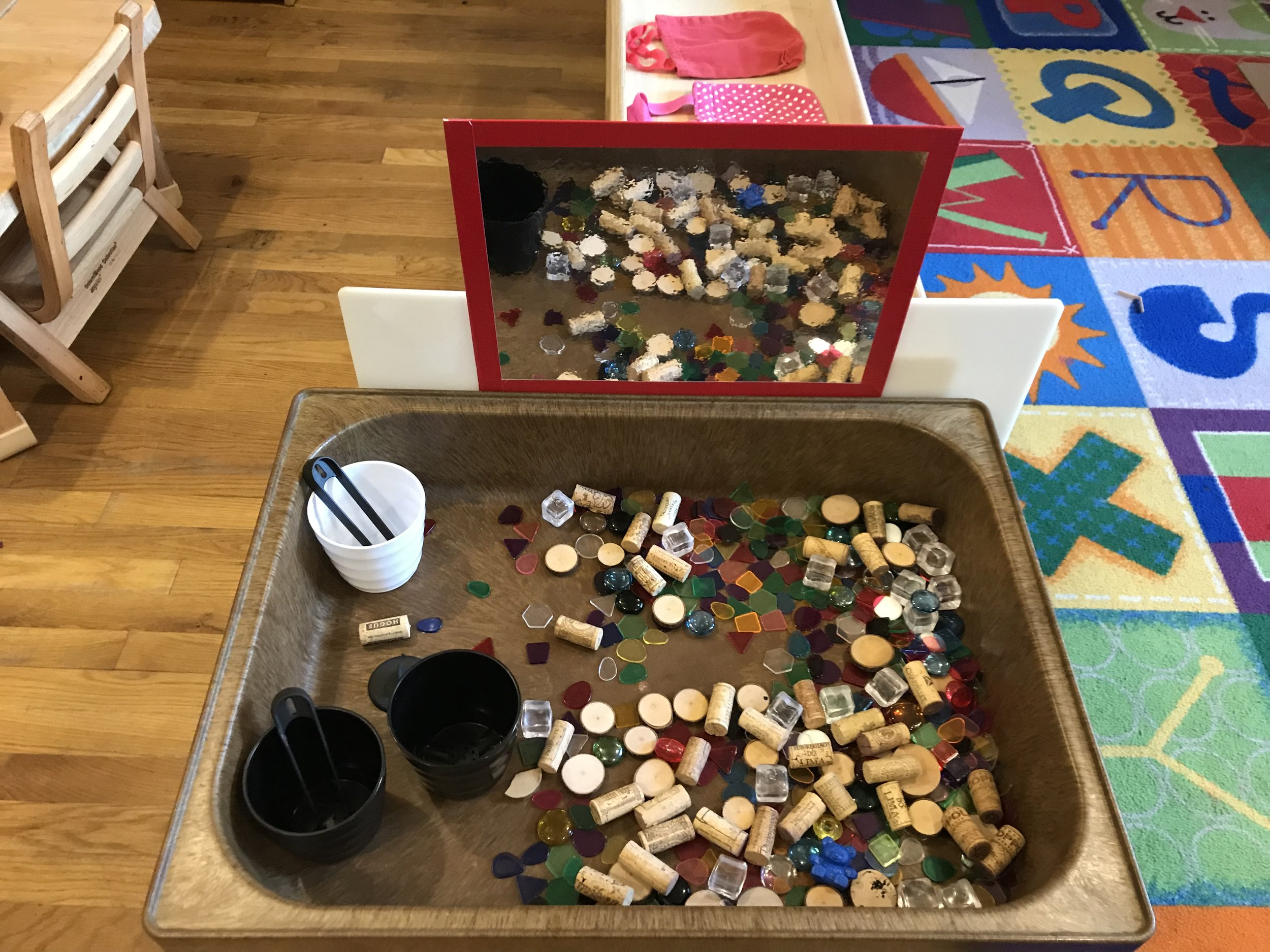 Reggio Inspired - Setting up the sensory table with loose parts to invite children to explore-we added the mirror as children have been enjoying looking at them selves