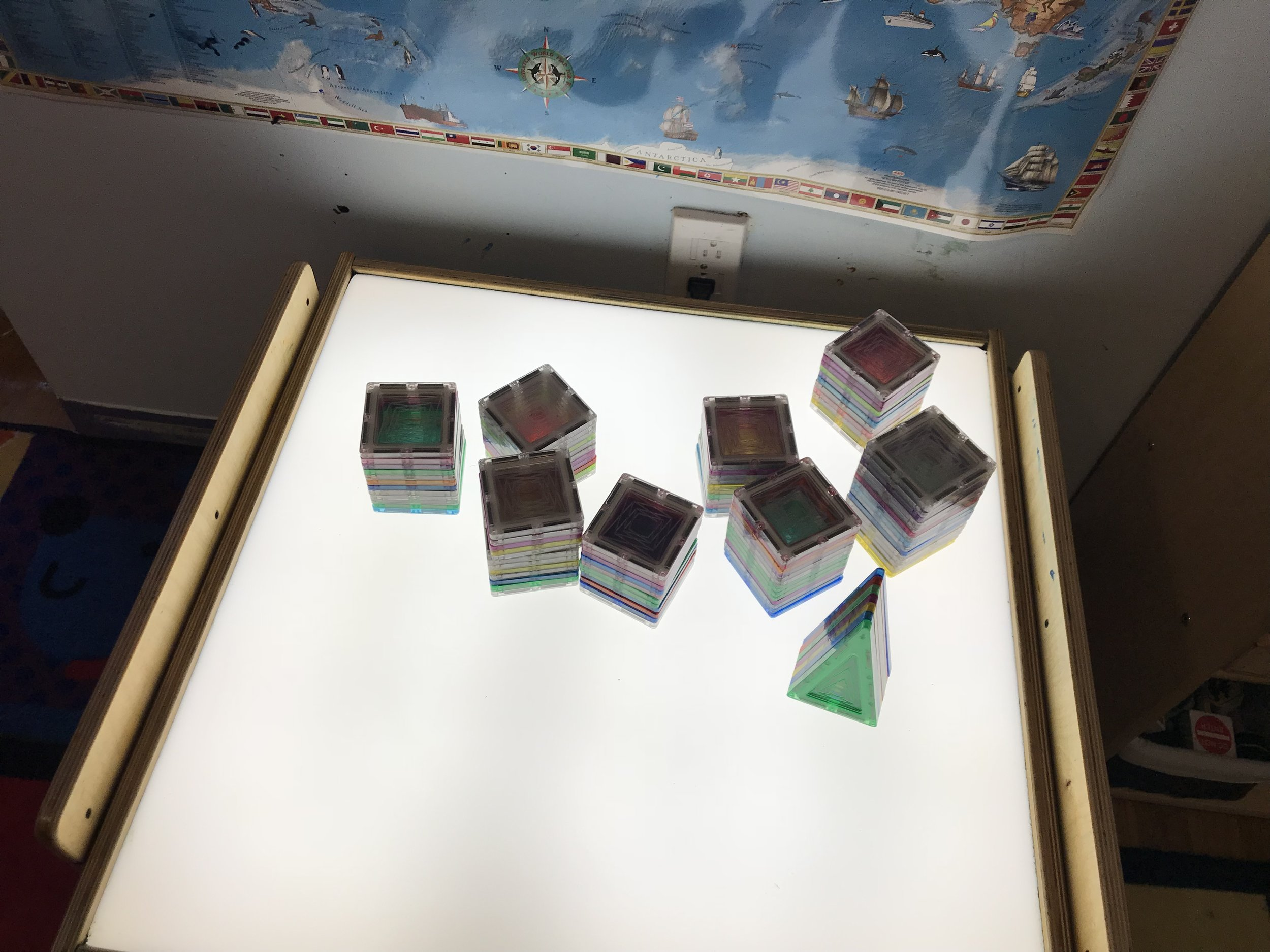 Reggio Inspired - Inviting children to build with magnet tiles on the light table to support children's interest in building