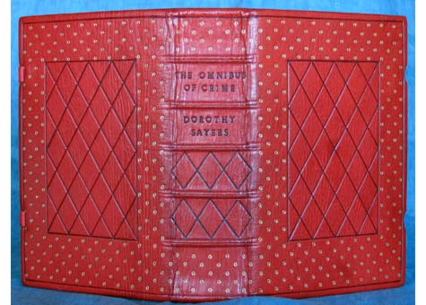 """Tom Conroy, """"The Omnibus of Crime"""" by Dorothy Sayers. Full scarlet Oasis leather binding with blind and gold tooling. Washed and gelatine sized; Herringbone sewing, laced in vellum spine linen over joins, back bead linen headbands over embroidered with yellow silk. Tight back, set for gape to provide tension against the clasps. Positive-spring clasps of brass with covering leather over vellum. Blue buckram dropspine box. 6 x 8 5/8 x 2 1/2."""