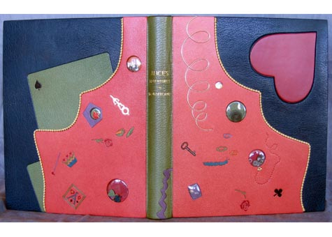 """Eleanore Ramsey, """"Alice's Adventures in Wonderland"""" by Lewis Carroll. Book covered in full teal French Cape morocco with a pink chagrin rabbit hole, in profile, extending onto front and back covers. Design represents Alice's fall through the rabbit hole focusing on the elements of time as used in the story. Front cover also inset with red heart in box calf. Doublure and fly leaf of teal suede. Book titled in gold on green French Cape morocco spine. Clam shell style box. 13 x 11"""". On loan from the Burstein Collection."""