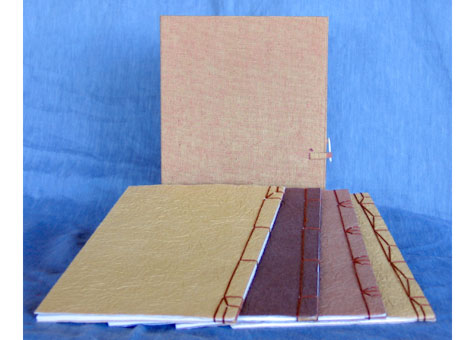 """Margaret H. Johnson, """"Blank Books"""" by Margaret Johnson. This is a set of 4 Japanese style bindings, each with a different style of sewing. They are enclosed in a textured paper-back silk wrapper and fastened with a bone fastener. 8 3/4 x 6"""