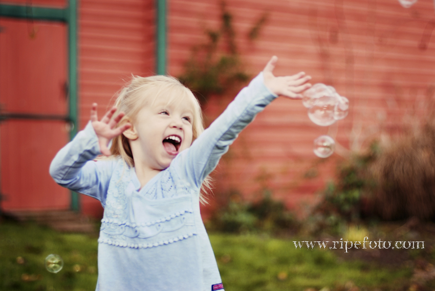 Portrait of little girl near red barn with bubbles by childrens photographer Ripe Photography.