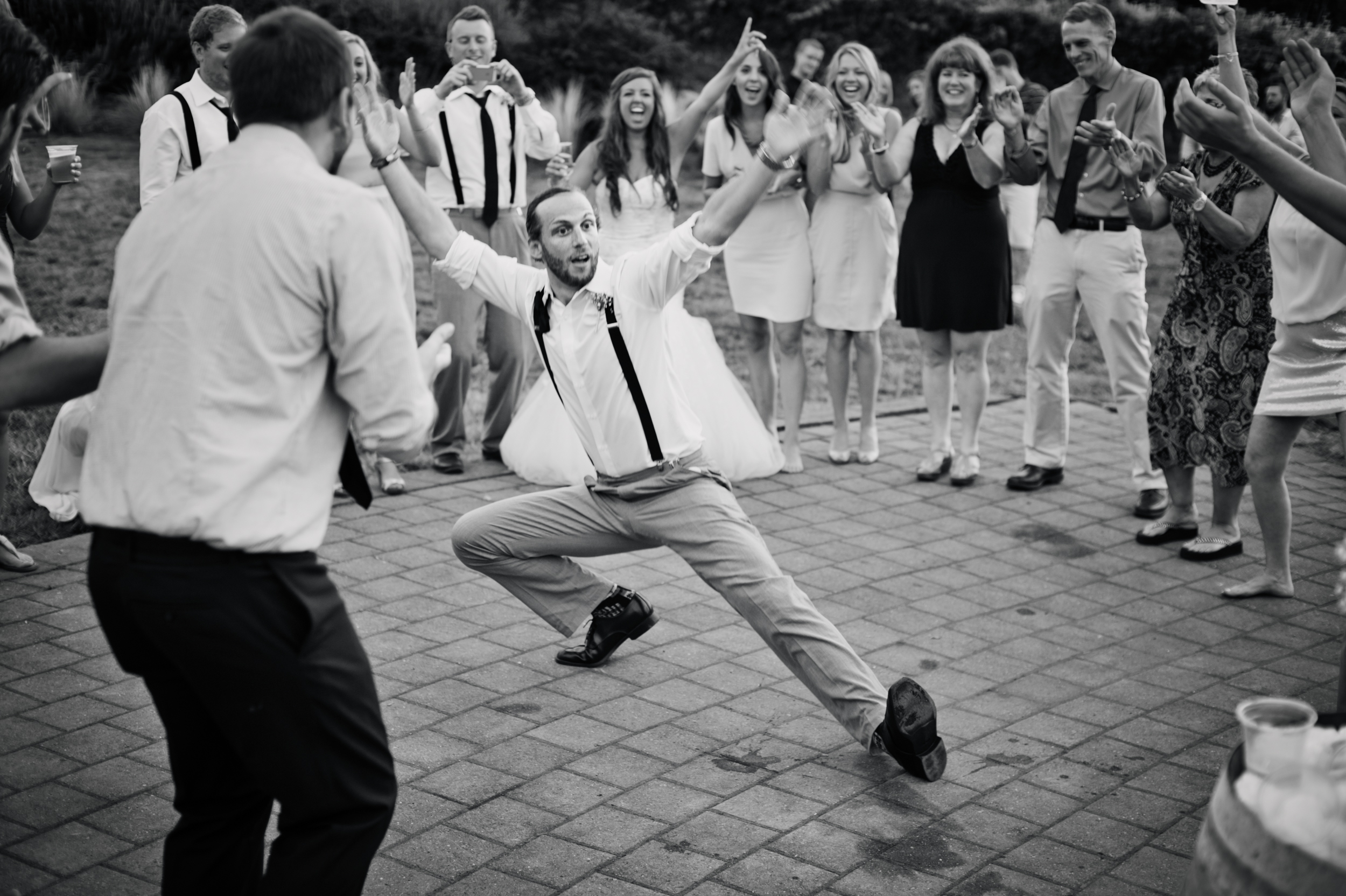 Portrait of man doing Russian Dance at wedding by Ripe Photography.