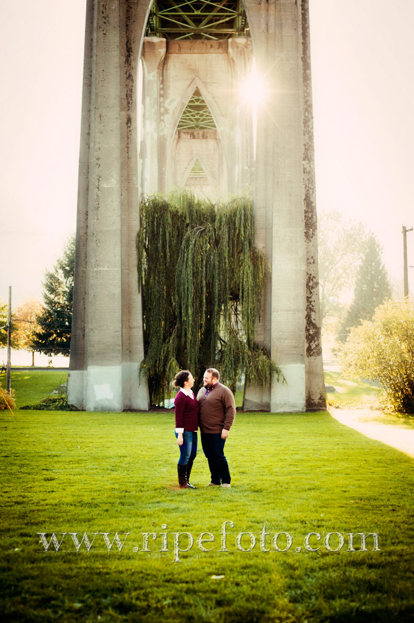 Portrait of couple under the St. John's Bridge in Cathedral Park in Portland, Oregon by Ripe Photography.