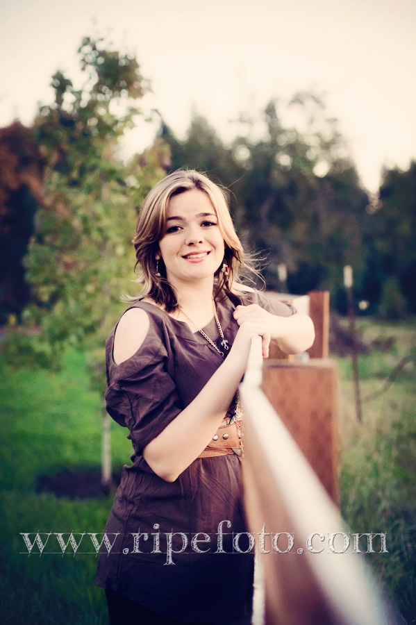 Portrait of teen girl on near fence by Ripe Photography.
