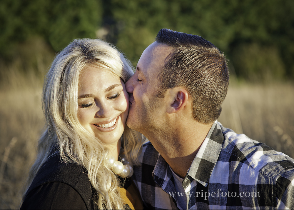 Portrait of happy couple in a field during the golden hour by Portland portrait photographer Ripe Photography.