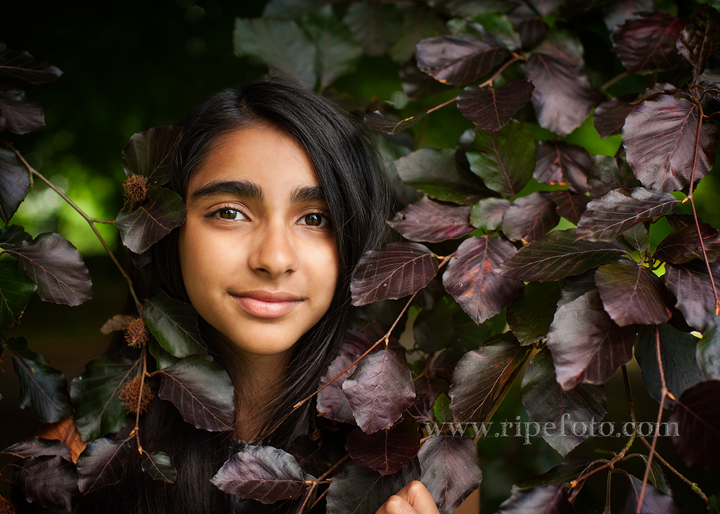 Portrait of girl on tree leaves background by children's photographers at Ripe Photography in West Yorkshire, England.