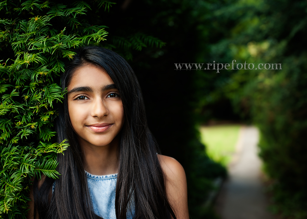 Portrait of girl on greenery background by children's photographers at Ripe Photography in West Yorkshire, England.