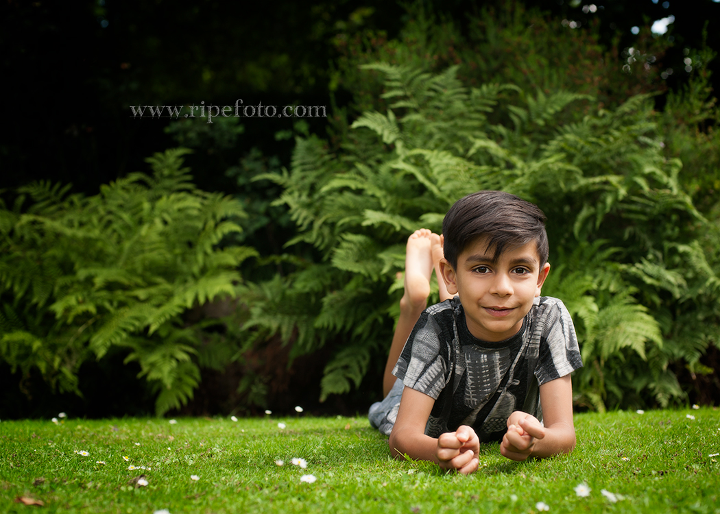 Portrait of boy on greenery background by children's photographers at Ripe Photography in West Yorkshire, England.