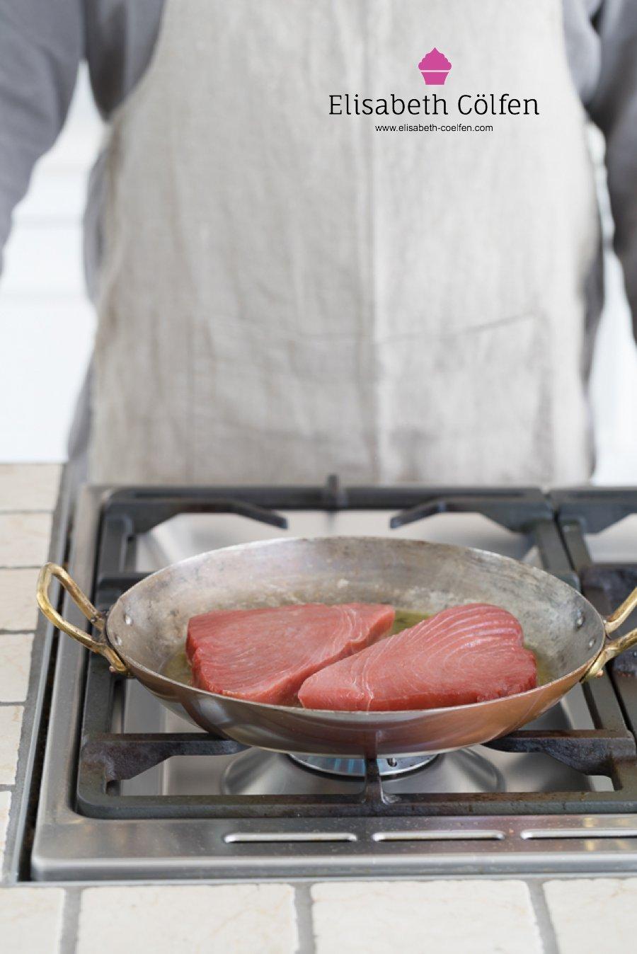 Mann brat Thunfisch in einer Kupferpfanne
