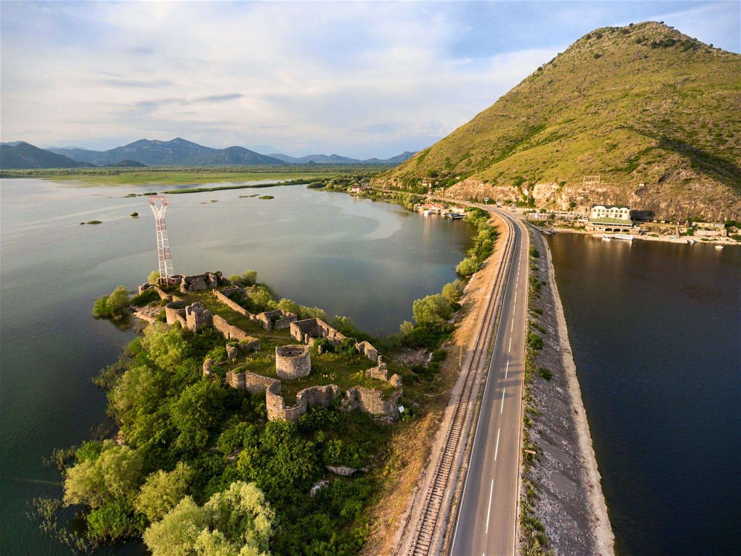 The train skirts the Lesendro Fortress ruins on Lake Skadar on its way to the Adriatic © Kekyalyaynen / Shutterstock